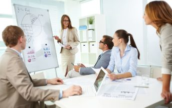 Confident top manager standing by the whiteboard and explaining her strategy at meeting